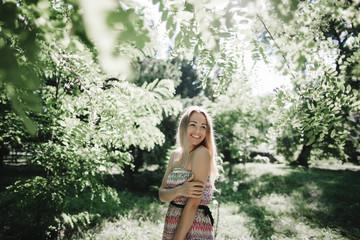 Caucasian woman standing near green trees