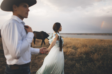 Caucasian woman holding hands with cowboy near river