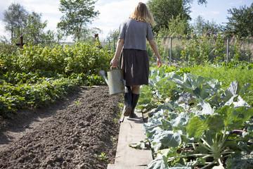 Caucasian woman carrying watering can in garden