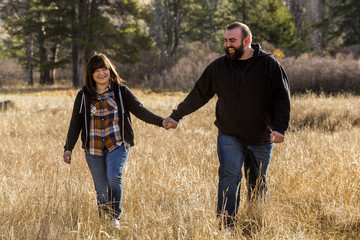 Caucasian couple holding hands in field