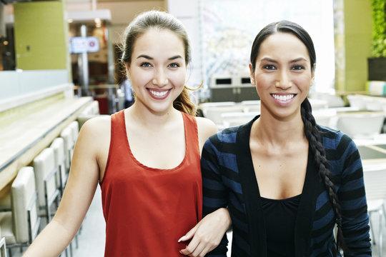 Smiling Mixed Race women posing in food court