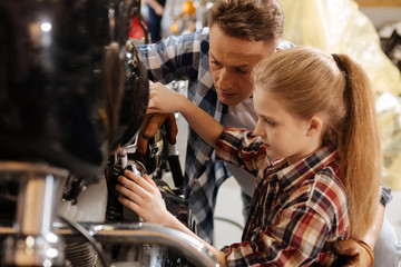 Cute girl and her dad fixing bike together