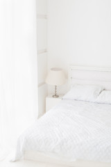 Total white room interior with bed, lamp, window with curtain