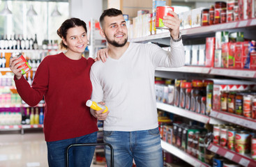 Clients buying tinned food at grocery store