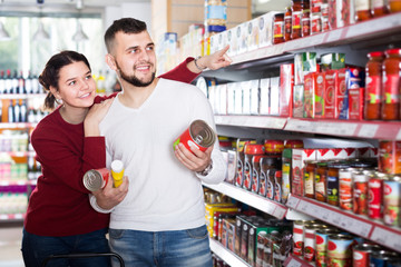 friendly couple choosing purchasing canned food for week at supermarket