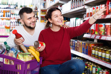 Couple standing near shelves with canned goods at store