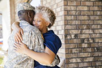Black soldier hugging wife on front stoop