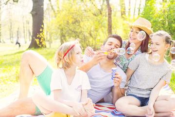 Familie im Park beim Picknick mit seifenblasen