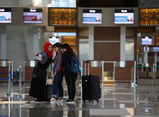 Domestic airline passengers take their picture in the international departure area of SoekarnoÐHatta International Airport's Terminal 3, which will open next week to international flights operated by Garuda Indonesia, near Jakarta