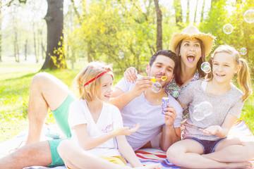 Familie im Park beim Seifenblasen machen