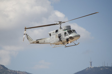 Helicopter bell uh 1 approach landing. right machine gun view. mountain background with aviation antenna