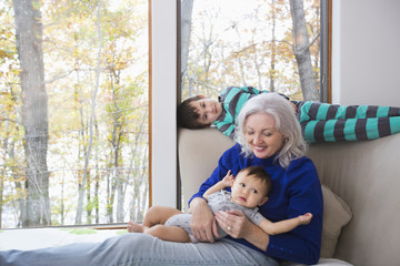 Smiling grandmother and grandsons near window