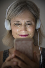 Smiling Caucasian woman listening to music on cell phone