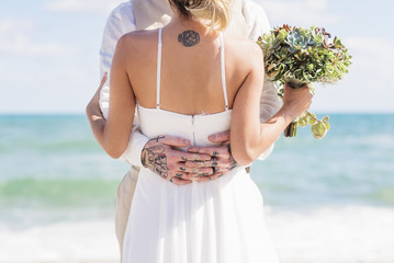 Caucasian bride and groom with tattoos hugging on beach