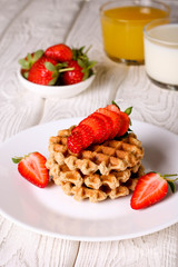 Waffels with strawberry on a white plate