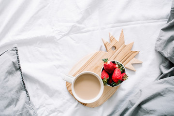 Breakfast in bed with coffee mug and strawberry. Bright grey linens. Flat lay, top view.