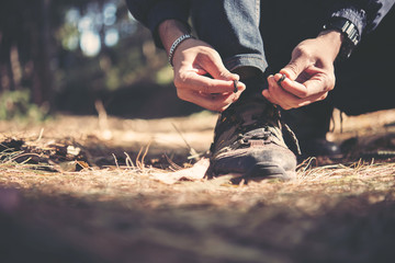 Tying the hiking boots of a hiker in the forset on mountian.