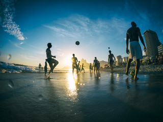 Silhouettes playing beach football on Ipanema Beach in Rio de Janeiro, Brazil