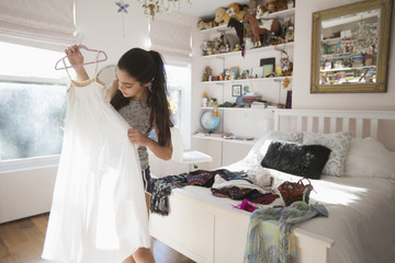 Caucasian girl examining white dress in bedroom