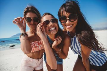 Playful beautiful women in sunglasses on the beach