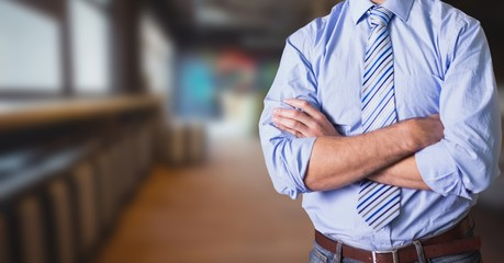 Midsection of businessman with arms crossed standing In office