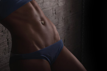 Closeup woman body part in blue panties. Sexy unrecognizable bodybuilder woman in blue bikini over stone wall background