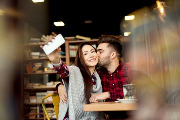 Self portrait making at restaurant couple enjoying together. Photo mobile posing for social networks.