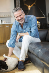 Caucasian man sitting on sofa petting dog