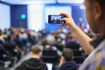 Audience at a business conference. Person taking photo with smart phone.