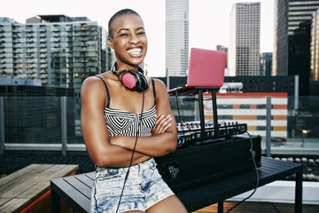 Smiling Black DJ relaxing on urban rooftop