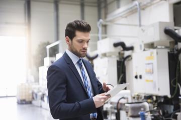 Businessman in factory shop floor using tablet