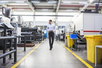 Man with tablet walking in factory shop floor