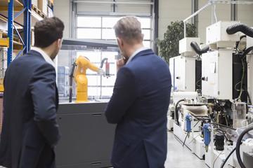 Two businessmen in factory shop floor looking at industrial robot