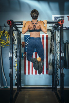 Caucasian woman doing chin-up in gymnasium