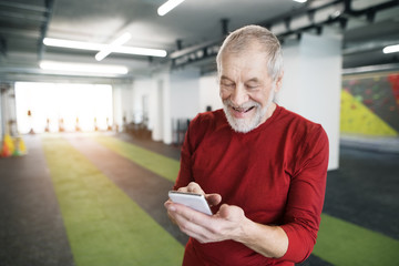 Fit senior man with smart phone in gym