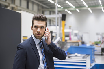 Businessman in factory shop floor on the phone