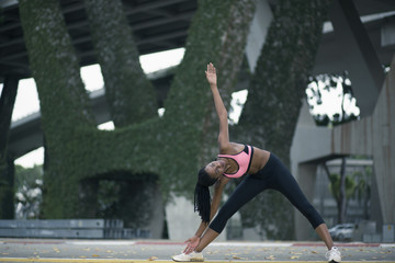Mixed Race woman stretching under bridge