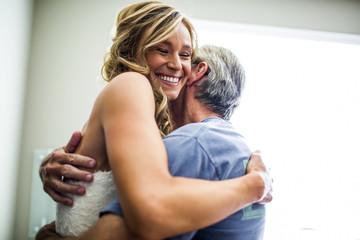 Caucasian bride hugging father