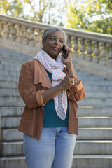 Black woman on stone staircase talking on cell phone