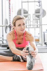 Woman stretching leg on exercise mat in gymnasium
