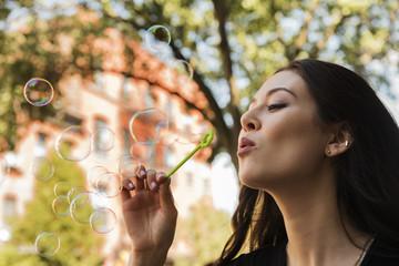 Thai woman blowing bubbles in park