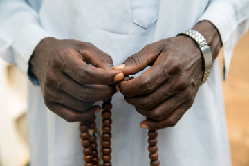 A Muslim holds Prayer beads outside a mosque in the town of Koui