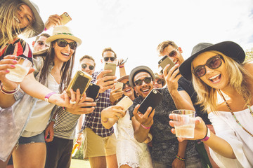 Friends posing for cell phone selfies
