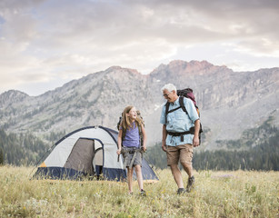 Caucasian grandfather and granddaughter camping on mountain