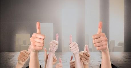 Digital composite image of hands gesturing thumbs up