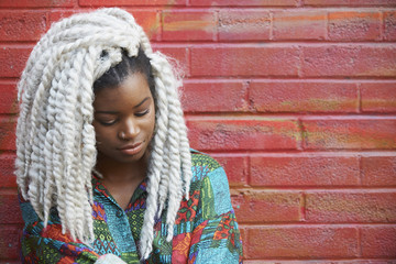 Serious Black woman leaning on brick wall