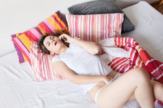 Sex on the phone. Young woman masturbating. Above view