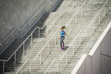 Caucasian woman running on staircase
