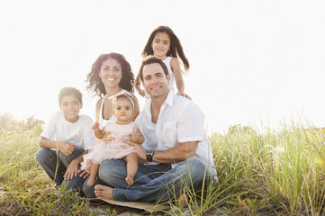 Portrait of Mixed Race family sitting in grass