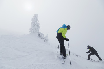 Skier standing up the slope whith epic mountains and clouds in the background
